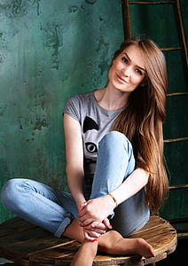woman in grey top and blue jeans sitting on brown spool table near brown ladder