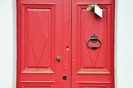 closed red wooden door with mails inserted at top