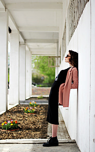 woman leaning on white painted wall
