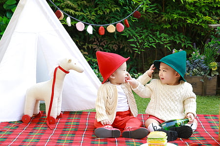 two babies sitting on red and green plaid textile