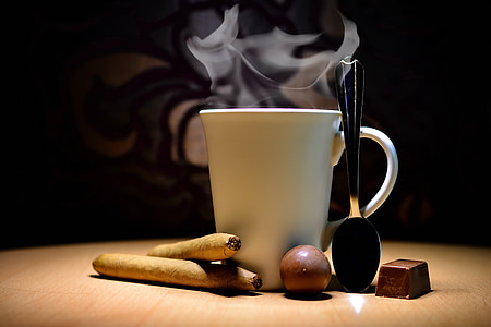 ceramic mug between spoon and cigars on table