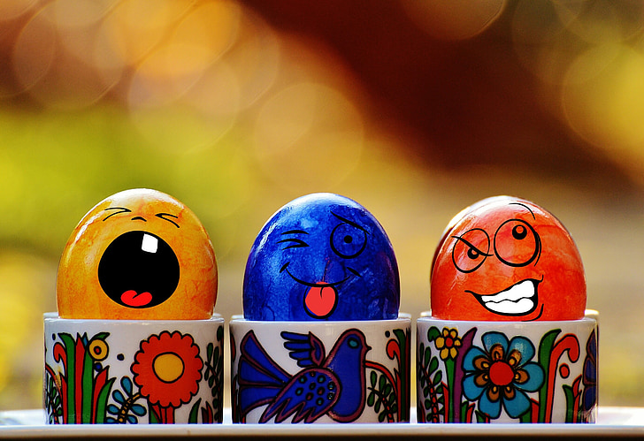 Royalty-Free photo: Three assorted-color egg decors on cup