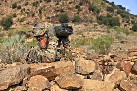 soldier behind rock using binocular