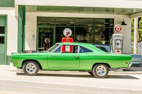green muscle car parked on gasoline station