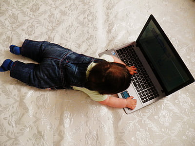 high-angle photography of baby playing laptop