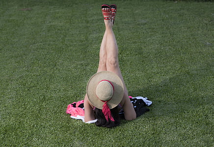 woman lying on green grass field