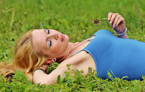 woman lying on grass with hand on head