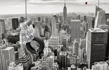 grayscale photo of girl hanging on swing at New York