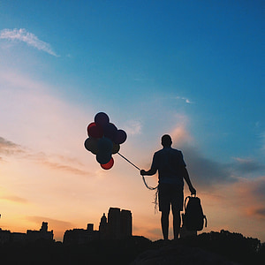 silhouette photo of person holding balloons and bag during golden hour