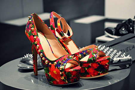 pair of red-green-and-black floral stiletto platform sandals on top of black table