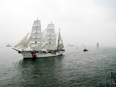white vessel on body of water with mist at daytime