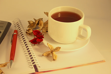 white ceramic teacup and saucer on notebook with flowers