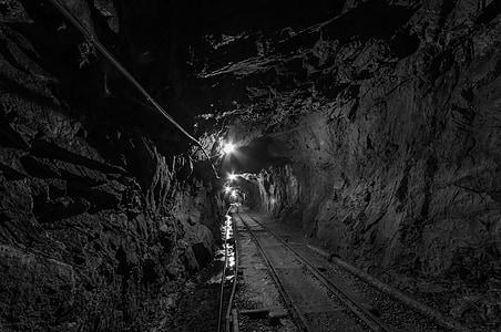 gray scale of train rail tunnel