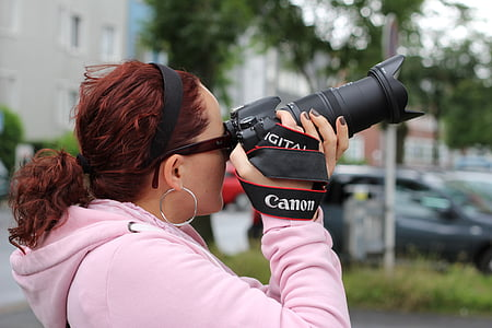 woman holding black Canon camera