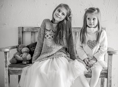 grayscale photo of two girls sits on bench chair with teddy bears