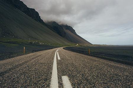 gray concrete road near green hill