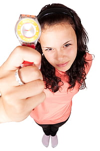 woman in pink top holding round silver-colored analog watch with red strap