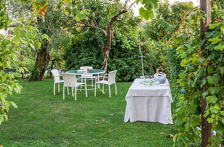 white and green patio set near table with white tablecloth near trees and green grass field at daytime