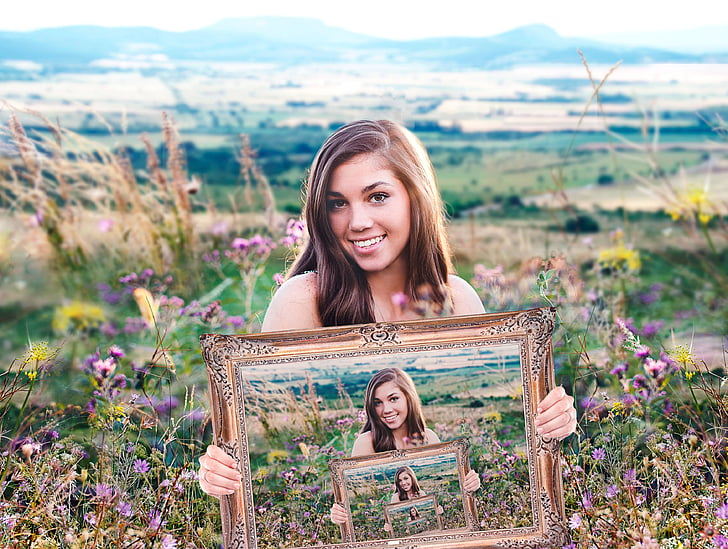 illusion photography of woman holding frame