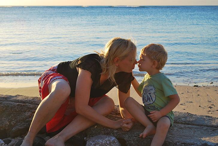 woman kissing toddler on seashore