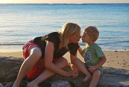 woman kissing toddler on seashore