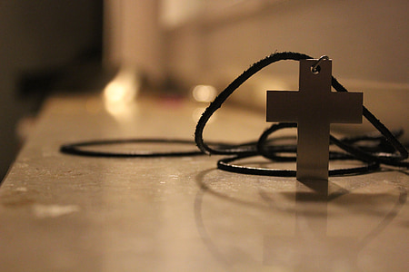selective focus photography of silver-colored cross pendant