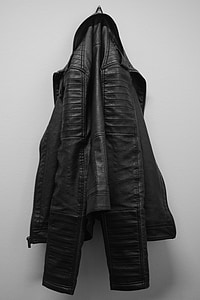 black leather jacket hanging on white wall