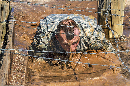 man crawling on mud under the barbwire
