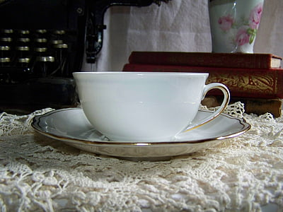white ceramic teacup on white plate