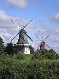 two red and gray wooden windmills surrounded with trees