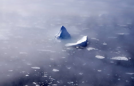 ice berg surrounded with fogs