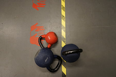 three assorted-color kettle dumbbells