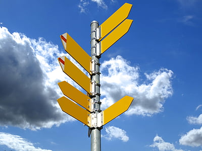 yellow left and right arrows signage under white clouds at daytime