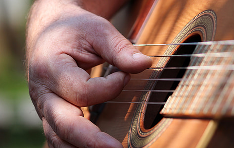 macro photography of man using guitar