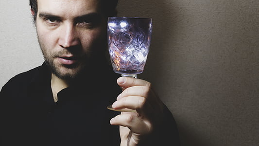 man in black top holding purple translucent drinking glass