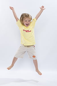 blonde haired child wearing yellow crew-neck shirt and beige shorts