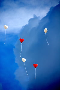 two red and three white heart balloons in the sky