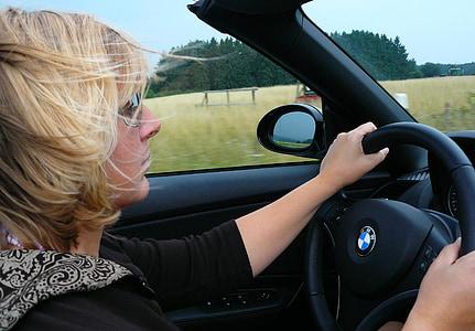 woman in black shirt driving a BMW car near green fields