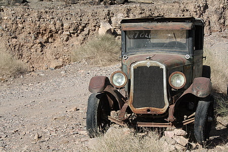 vintage brown and black car parked over dry ground with dried plants near rock formations