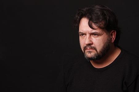 man wearing black crew-neck shirt with dark background