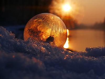 amber glass ball on snow