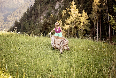 girl pushing a wheelbarrow in forest