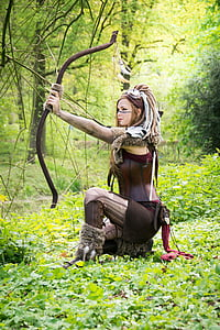 woman in brown costume holding bow