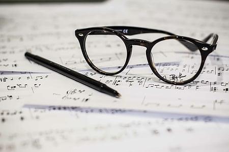 black framed eyeglasses beside black pen