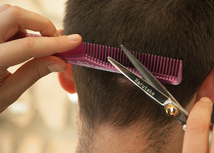 person cutting person's hair using scissors and comb