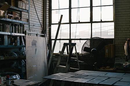 gray A-frame ladder beside pedestal fan near window