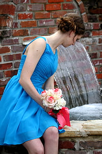 woman in blue spaghetti strap dress holding bouquet of flowers