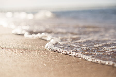 body of water with brown sand at daytime