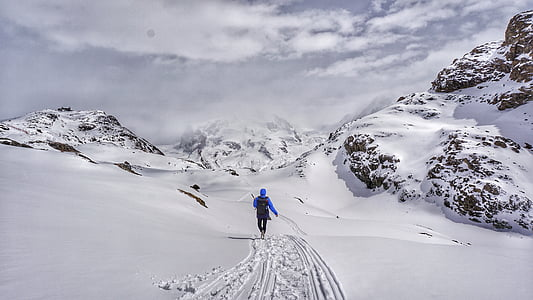 person in blue jacket walking on snowfield at cloudy sky