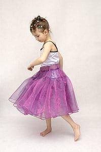 girl wearing purple tutu skirt and white camisole